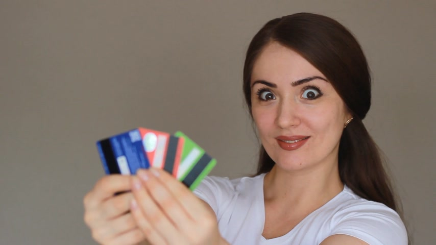 decisões : Portrait of a young beautiful woman close-up, who is smiling, looking at the camera and holding credit bank cards of different colors and banks. The concept of choosing and saving credit, finance, and economy. Stock Footage