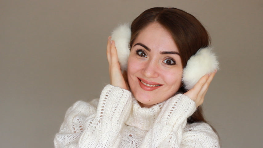 fur headphones : Portrait of a young beautiful woman close-up in warm winter headphones and a white sweater on a light background. A cute happy girl smiles, laughs and looks at the camera