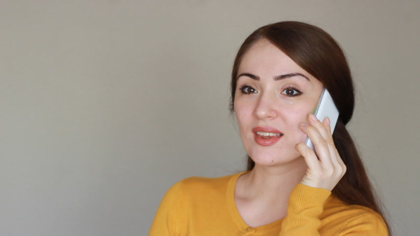 código : Beautiful young brunette woman talks on the mobile phone, smiling and says i love you. Happy girl with a white smartphone in her hand on a light background looks at the camera.