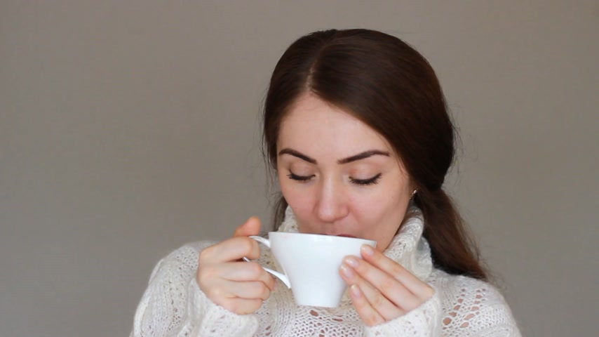 watching news : Young beautiful woman in a warm winter sweater drinks a hot drink from a white cup and looks at the camera. The girl enjoys the aroma and takes a sip. Close-up. Stock Footage