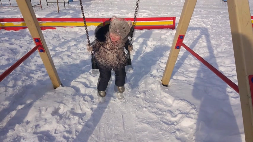 snow caps : Mother woman walks in the open air with child daughter. Little girl swing on winter playground. Snow and frosty cold weather
