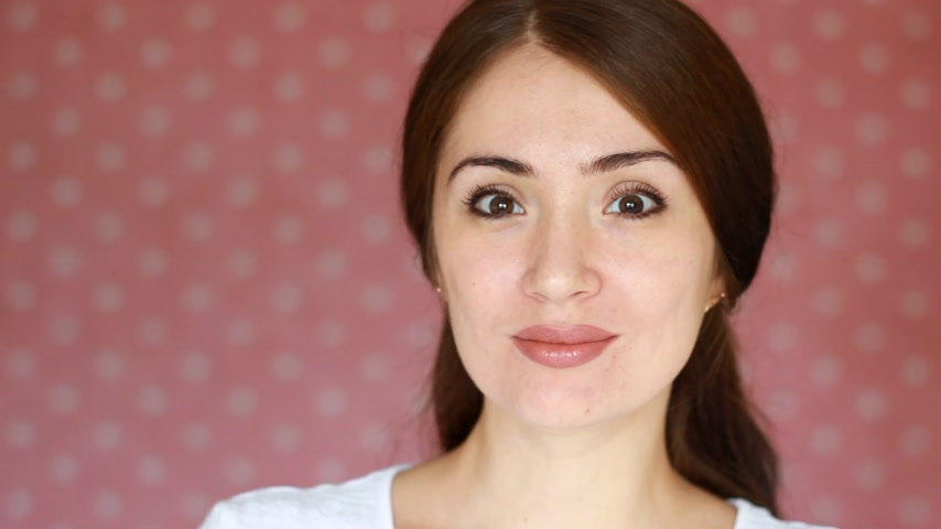 código : Beautiful happy girl smiling, says i love you and looking at the camera. A young woman is holding a candy in the shape of a heart. Stock Footage