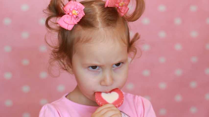 леденец : Funny little girl eating a lollipop with a picture of the heart. A happy cute child holds a candy in his hand and expresses different emotions - smiling and and laughs. Close-up.