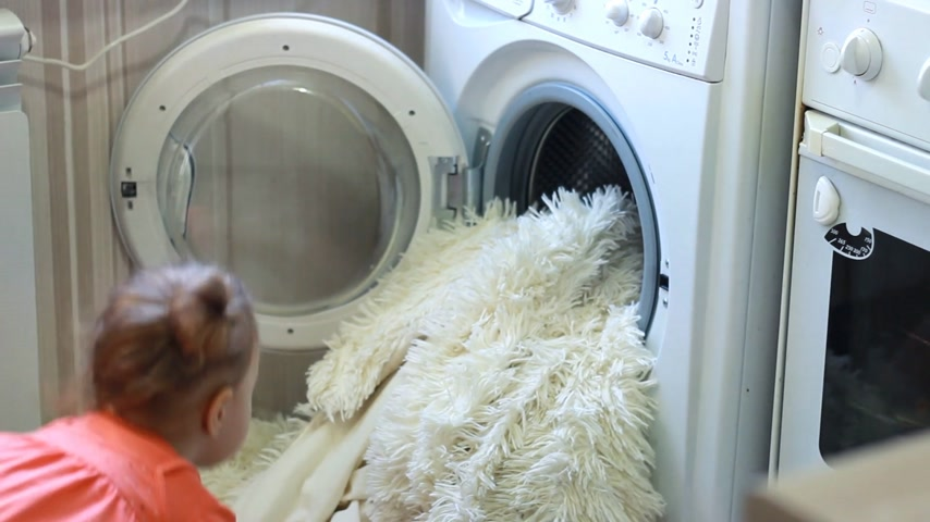 linen : Funny cute little girl puts dirty things in the washing machine. Baby and laundry.