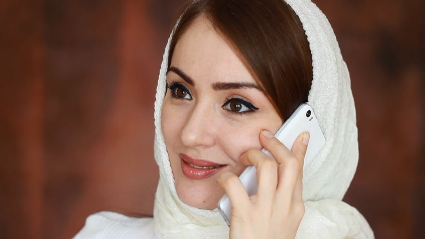головной платок : Portrait close-up of a beautiful Arab woman in a traditional headscarf hijab communicates on a mobile phone. A Muslim girl speaks on a white smartphone and smiles.