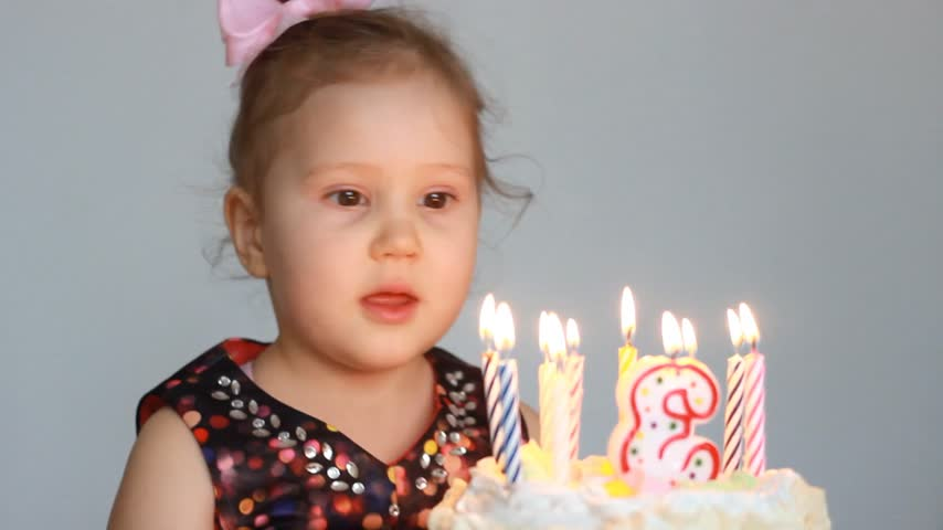 cakes : Funny happy child blows out candles on birthday cake at party. Cute little girl. The concept of a childrens holiday. 3 years.