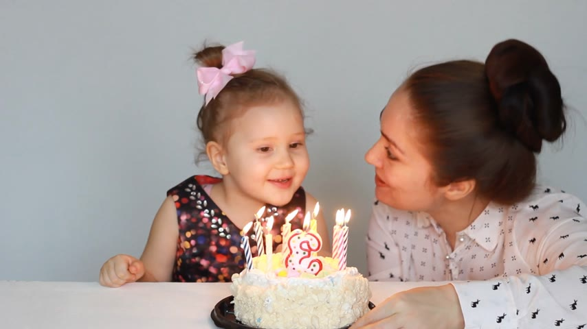 felicitação : Happy mom and child look at the flame of a candle on birthday cake at party. Mother Congratulates, embraces and Kisses Her Daughter. 3 years. Stock Footage