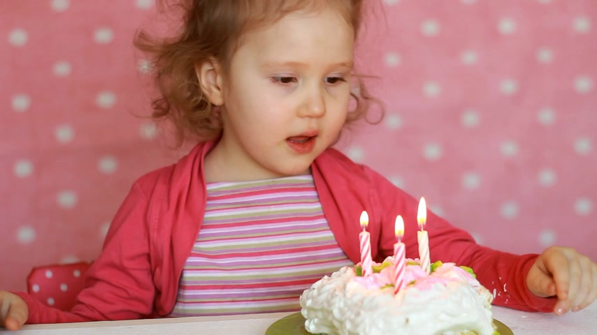 home studio : Funny happy child blows out candles on birthday cake at party. Cute little girl. The concept of a childrens holiday. 3 years.