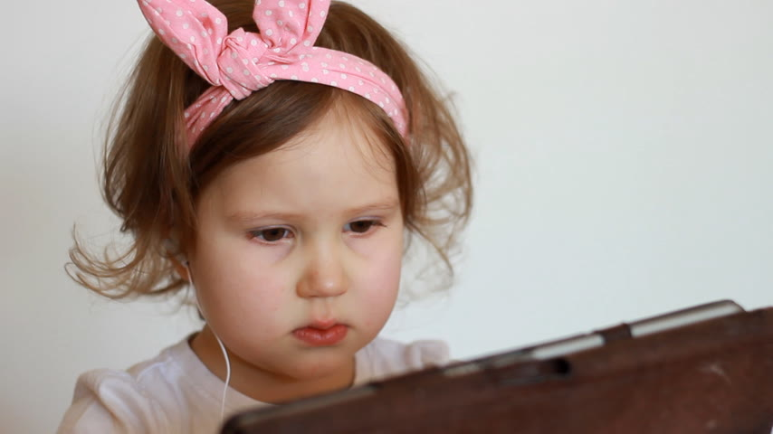carelessness : A cute little girl thumbs a playlist on the tablet, smilling and listens to the song in the headphones. Funny child with a pc in his hands chooses an application for listening to music. Close-up portrait Stock Footage