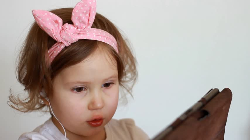 cheerfulness : A cute little girl thumbs a playlist on the tablet, picks and listens to the song in the headphones. Funny child with a pc in his hands chooses an application for listening to music. Close-up portrait