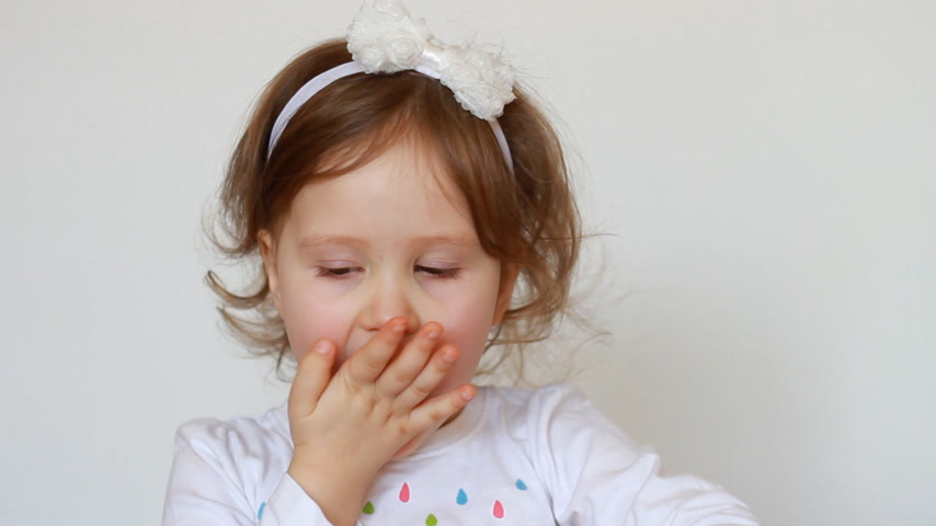 souffle : Funny little girl eating a candy. A happy cute child expresses different emotions - smiling and teasing. Close-up.