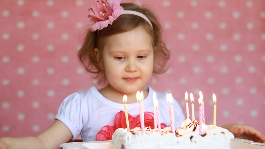 explodindo : Cute happy child make a wish and blows out candles on birthday cake at party. Funny little girl. The concept of a childrens holiday. 3 years, pink background.