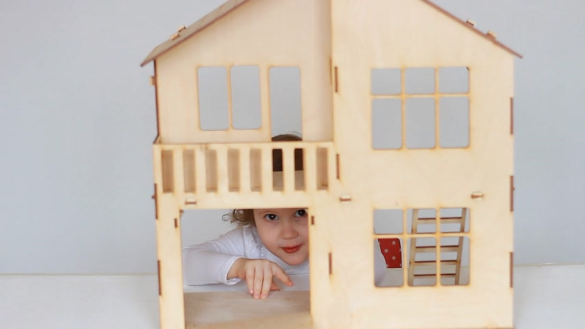 swatches : Funny cute little girl smiling and waving her hand from the breadboard model of a wooden house. The concept of childhood and child protection. The child plays the game.
