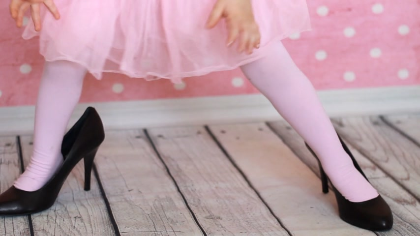 pięta : A child in adult shoes on a pink background. Glamor. Fashion. Girl fashionista. Baby legs in mothers shoes. Black female shoes with heels. Close-up.