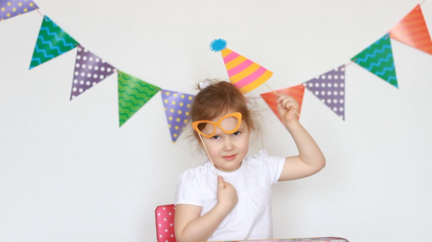 tatarak : Portrait of a cute little girl on a light background with colored flags, which tries on the decor of glasses and a hat for celebrating a happy birthday. Child and party, masquerade, festival.