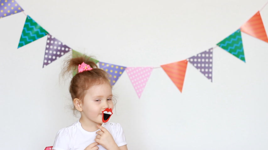 tatarak : Portrait of a cute little girl on a light background with colored flags, which tries on the decor for celebrating a happy birthday. Child and party, masquerade, festival