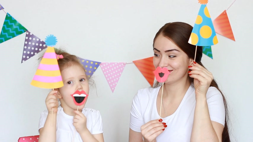 tatarak : Mother and daughter smile and laugh, try on different decorations to celebrate the holiday. The concept of a holiday, party, birthday, decor for celebration. Portrait of a young woman and a child close-up.