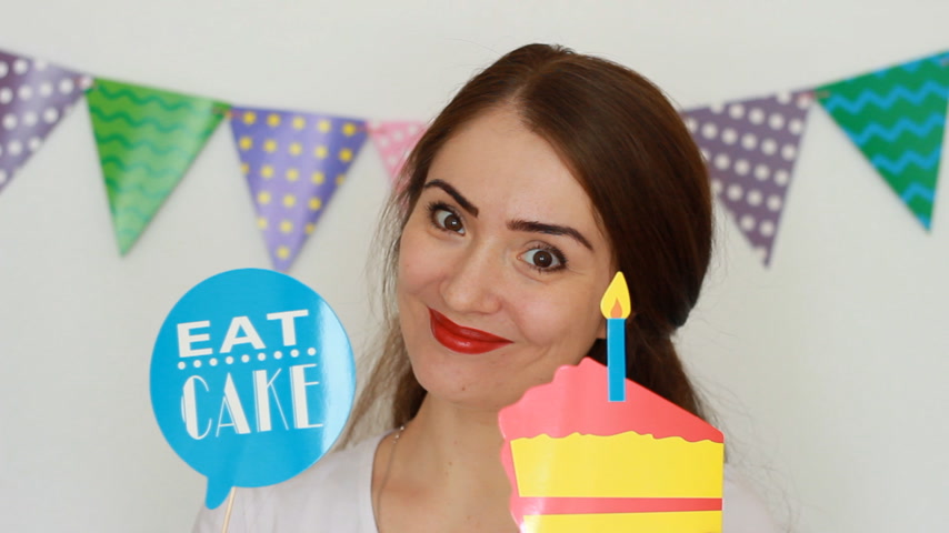 tatarak : The funny girl smiles, holds in hands cake and blows out a paper candle. Portrait of a young happy woman close-up. Concept of a holiday, birthday, decor for celebration. Wideo