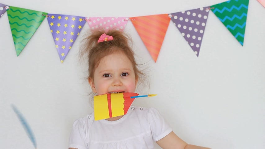 tatarak : Portrait of a cute little girl on a light background with colored flags, which keeps the decor for celebrating a happy birthday. Child and party, masquerade, festival