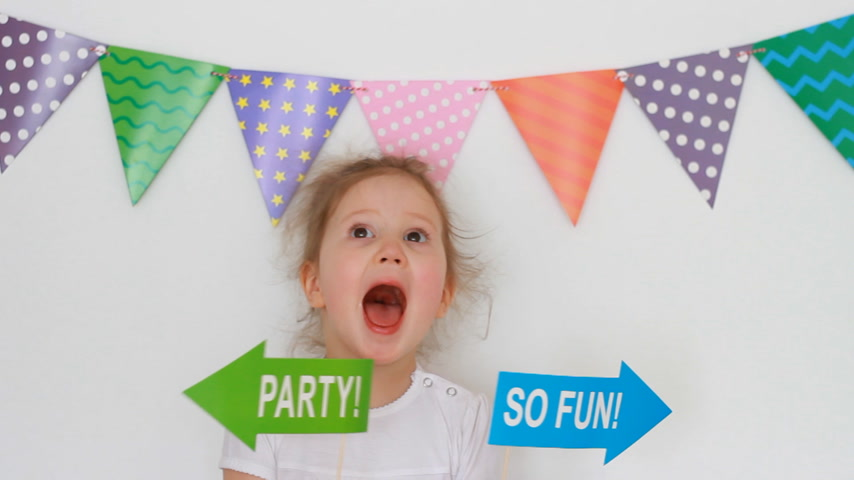 tatarak : Portrait of a cute little girl on a light background with colored flags and decor for celebrating a happy birthday. The child holds in his hands the tablets - the party and s fun, rejoices and laughs
