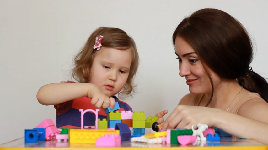 construtor : Educator and little girl playing together sitting at the table. Girl busy with his building constructor, teacher watching, talking and helps child. Development and education of preschoolers