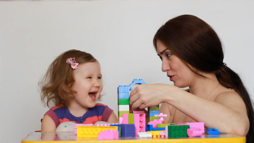 construtor : Mother and her little daughter playing together sitting at the table with constructor. The child begins to be capricious and cry, mom tries to calm the baby
