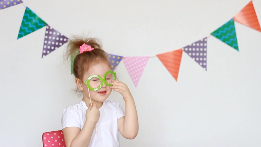 tatarak : Portrait of a cute little girl on a light background with colored flags, which tries on the decor of glasses for celebrating a happy birthday. Child and party, masquerade, festival Wideo