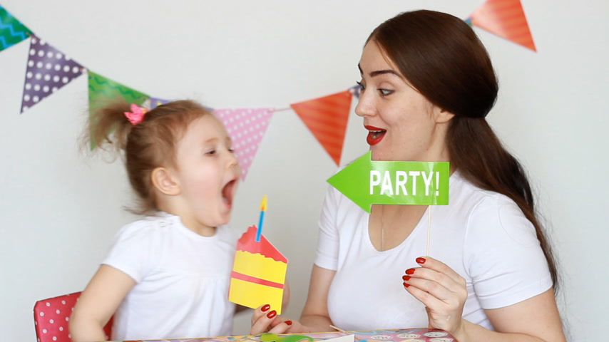 tatarak : Mother and daughter have fun, smile and laugh and different decorations to celebrate the holiday. The concept of a holiday, party, birthday, decor for celebration. Portrait of a young woman and a child close-up