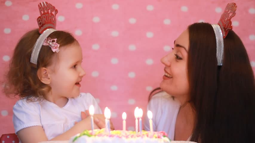 felicitação : Happy birthday. Mother and child make a wish and blows out candles on cake at party. Mom Congratulates, embraces and Kisses Her Daughter on a pink background. Stock Footage
