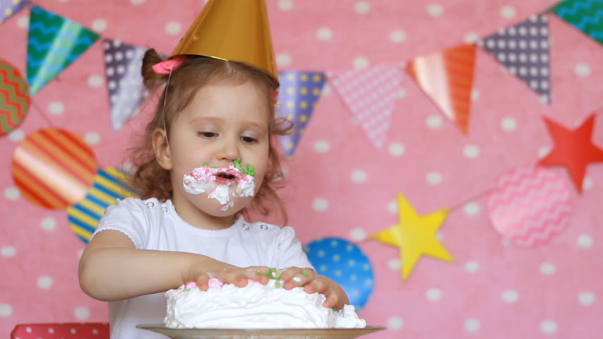 gyengéd : Dirty hands of a child in a cake. Birthday and party. Funny girl licks her fingers with dessert
