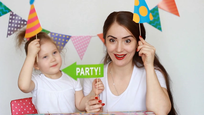 tatarak : Party. Happy birthday. Mother and daughter have fun, smiling and laughing and different decorations to celebrate the holiday. The concept of a holiday. Decor for celebration. Portrait of a young woman and a child close-up Wideo