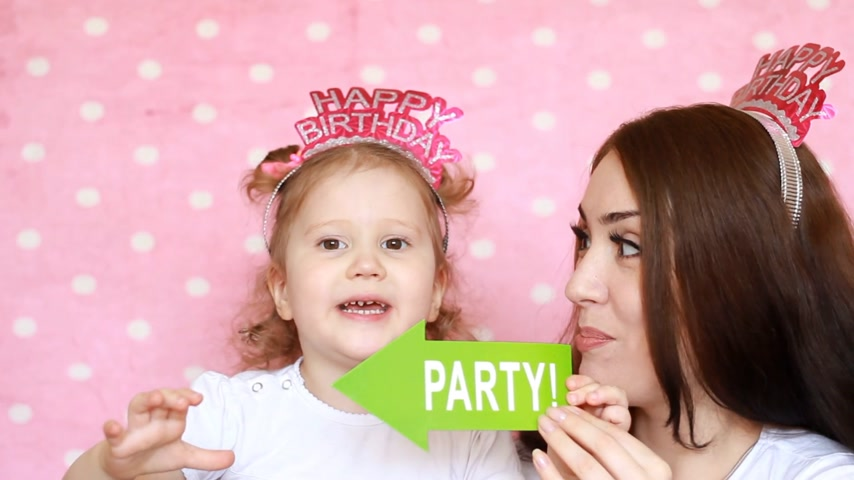 home studio : Party. Happy birthday. Mother and daughter play together and laugh.The concept of a holiday, decor for celebration. Portrait of a young woman and a child close-up Stock Footage