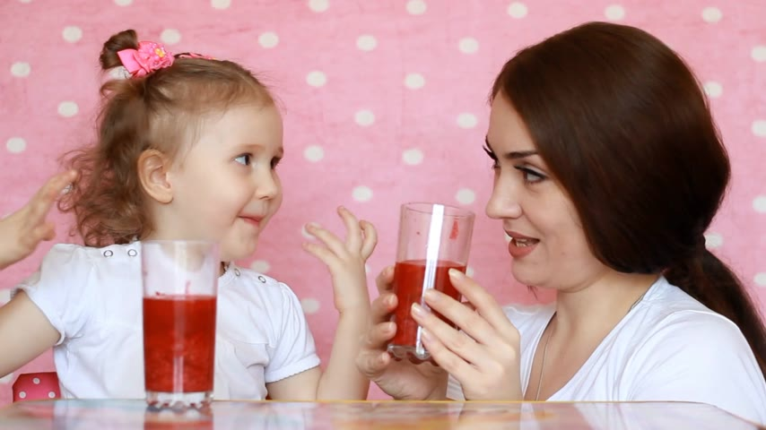вегетарианство : Mother and daughter are drinking smoothies, smiling. Young woman with her child enjoying a refreshing tasty drink. Pink background