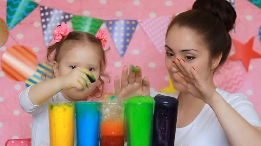 образованный : Mother and child are doing an experiment with colored foam. Dirty hands in paint. Study color for children. Multicolored liquid. Development of a preschooler.