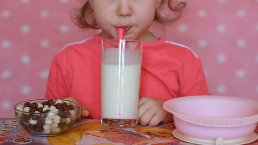 yoghurt : The child drinks a milk drink - kefir, smoothies, cocktail, yogurt. A nice little girl holding a glass in her hands and drinking through a straw