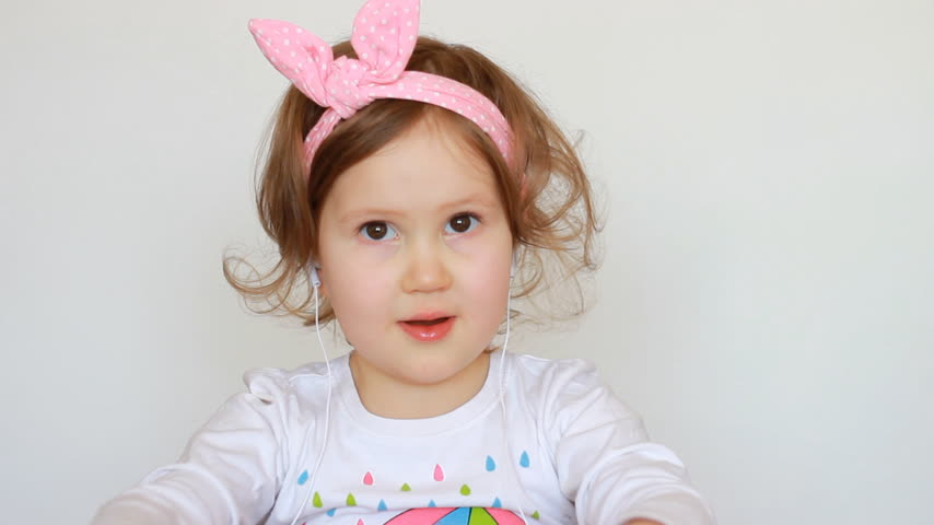 cheerfulness : A cute little girl in the headphones listens to the song. The concept of music and relaxation. Close-up Funny child portrait Stock Footage
