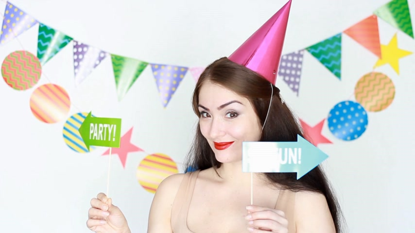 tatarak : Happy birthday. The funny girl in a pink festive cap smiles and holding a sign of the party. Portrait of a young happy woman close-up Wideo