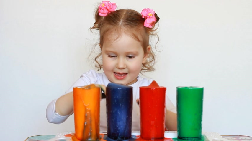 művelt : Child and science experiment. Entertainment for children. preschool education. Multicolored drinks. A cute little girl and dirty her hands.