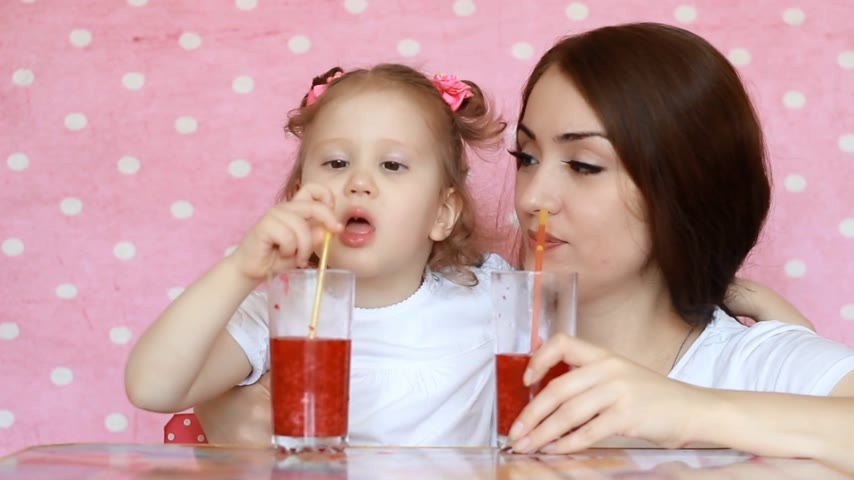vejetaryenlik : Mother and daughter drink smoothies through a straw and smile. Close-up portrait of a young woman with her baby who enjoy a refreshing delicious drink. Pink background Stok Video
