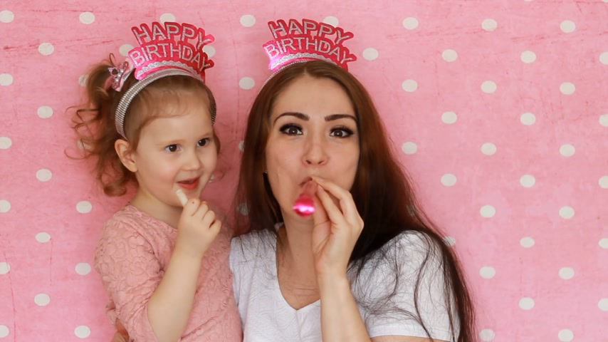 růžky : Happy birthday. A woman and her child smiles, have fun, laugh and celebrate, blowing party horns. Close-up portrait Mother and daughter on pink background. Dostupné videozáznamy
