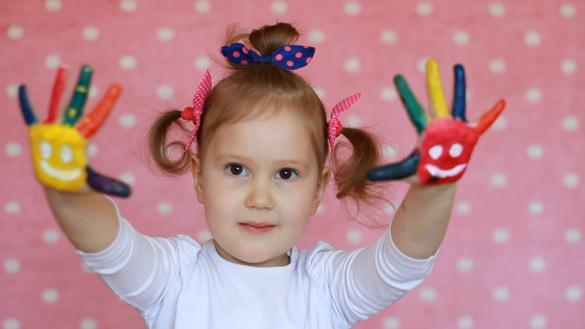 pintado : Child girl with dirty palms in paint. Happy little baby with colorful painted hands with smiles on a pink background. Education concept