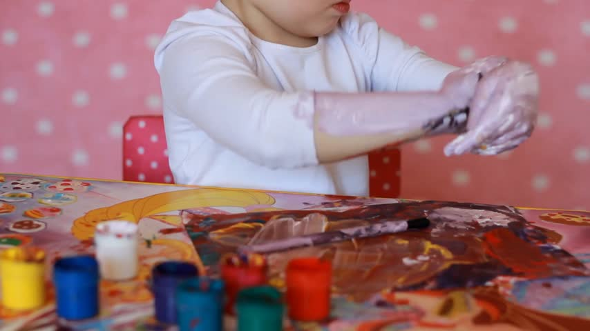 sanatçılar : Funny child paints his hands with paint. Baby artist. Little girl draw body art.