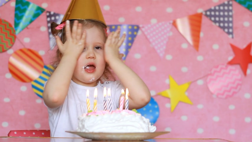 uç : A child girl blows out candles on a birthday cake and eats it with his finger. Baby makes a wish
