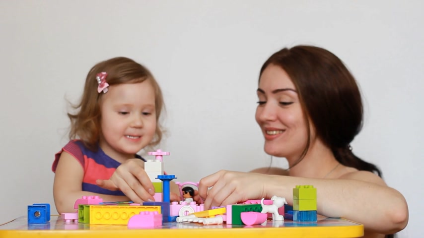 przedszkolak : Mother and girl child busy building a constructor.