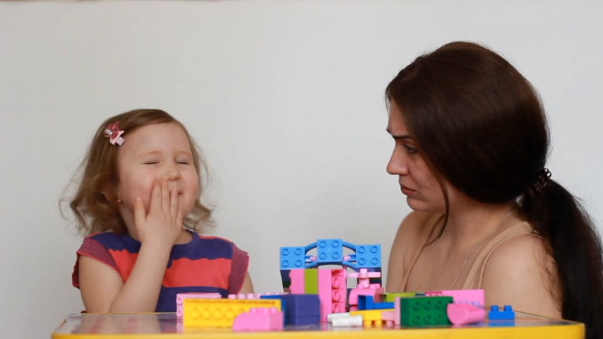 ilginç : Baby girl capricious and cry, mother tries to calm the baby, Hugs and comforts. Mom and her child playing together with constructor. Stok Video