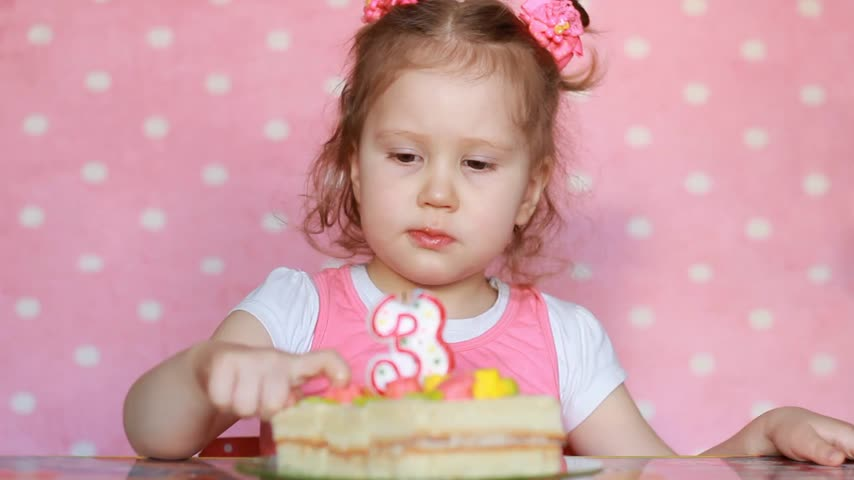 kinderwens : A sweet little girl make a wish and blows out candles on birthday cake at party. Cute child. The concept of a childrens holiday. 3 years, pink background.