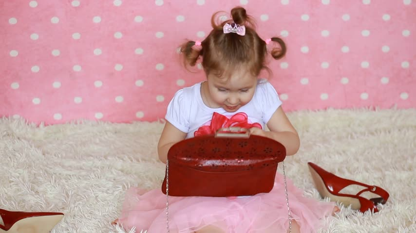 каблуки : Glamour. Fashion. Fashionista. Cute little girl dresses red sunglasses in the shape of hearts. Pink background. Funny child smiles and laughs. Стоковые видеозаписи