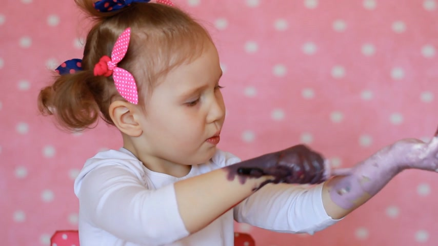 гуашь : Funny child paints his hands with paint. Baby artist. Little girl draws art