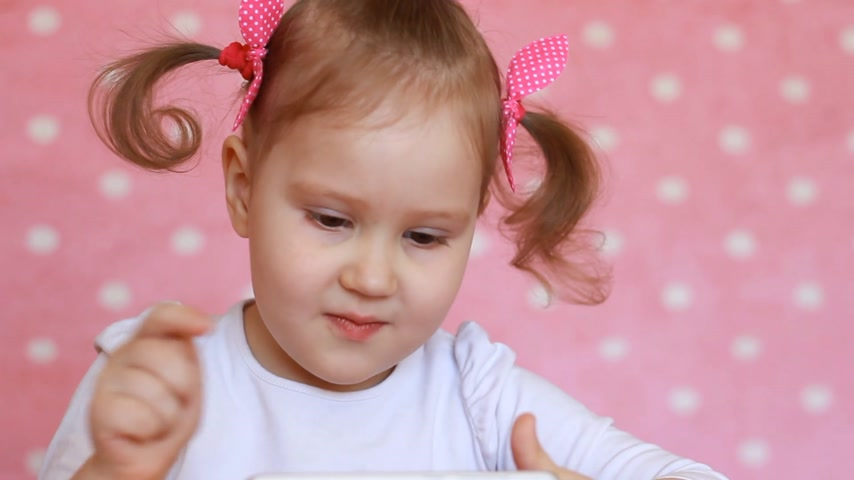 elektronický : Child girl playing with a mobile phone. Baby uses a game application on the smartphone. Potrait closeup
