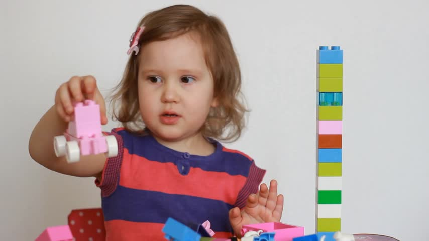 interessado : Child girl busy building a constructor. Baby develops his thinking and building skills in the game.